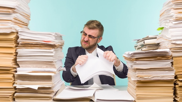 オフィスで働いている経営者と書類の山、彼は仕事でいっぱいです。紙の契約を破り、仕事を辞める-画像