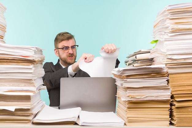 オフィスで働いている経営者と書類の山、彼は仕事でいっぱいです。紙の契約を破り、仕事を辞める-