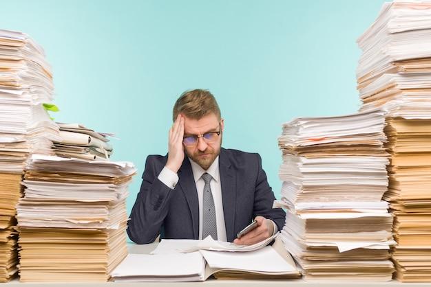オフィスで働いている経営者と書類の山、彼は仕事でいっぱいです