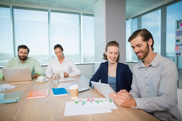 Business executives discussing over digital tablet in conference room