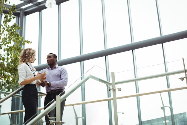 Business executives discussing near staircase