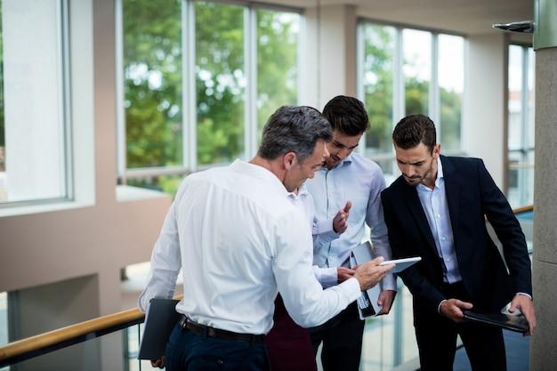 Руководители бизнеса обсуждая над цифровым планшетом