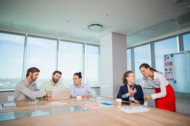 会議室で互いに議論する企業幹部