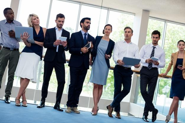 Business executives holding mobile phone, digital tablet, laptop