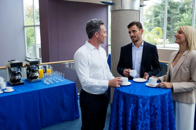 Business executives interacting with each other while having coffee