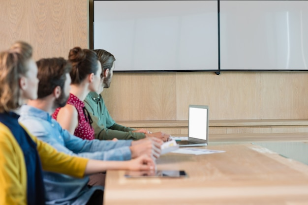Business executives listening to a presentation in conference room
