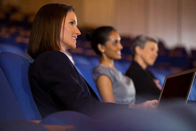 Business executives listening to speech at conference center