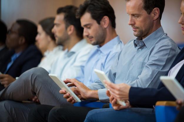 Руководители предприятий, участвующие в деловой встрече с помощью цифрового планшета в конференц-центре