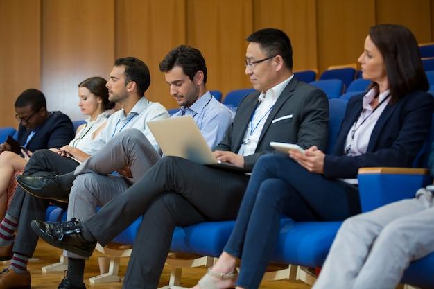 Руководители предприятий, участвующие в деловой встрече с помощью электронных устройств в конференц-центре