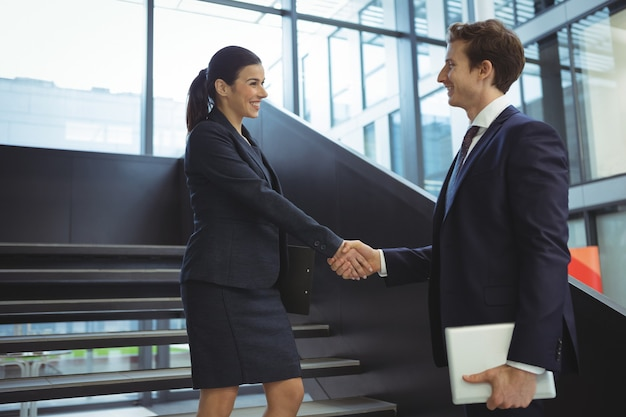 Business executives shaking hands on stairs