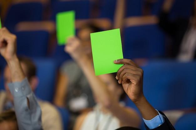 Руководители предприятий демонстрируют свое одобрение, поднимая руки в конференц-центре
