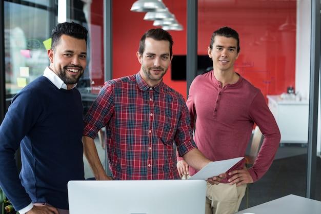 Руководители бизнеса стоя с документом в офисе