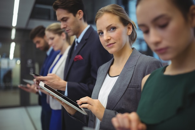 Руководители предприятий, использующие электронные устройства в коридоре