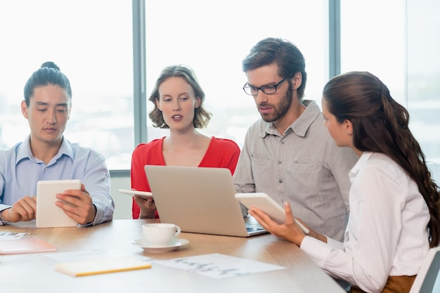 Business executives using laptop and digital tablet in conference room