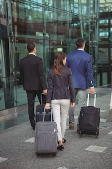 プラットフォームの外のスーツケースを持って歩く経営者