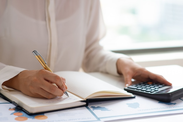 Business expert analyzing reports and counting expenses