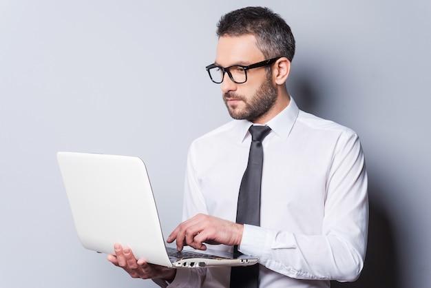 직장에서 비즈니스 전문가입니다. 회색 배경에 서서 노트북 작업을 하는 셔츠와 넥타이를 입은 자신감 있는 성숙한 남자