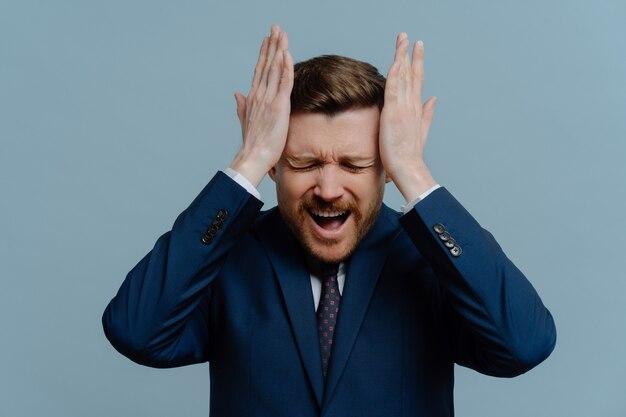 事業の失敗。不幸せな欲求不満のビジネスマンまたはスーツを着た男性起業家が頭を抱え、大声で叫ぶ