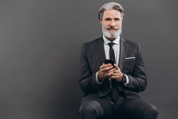 Business and fashionable bearded mature man in a gray suit sitting and using phone on the grey wall.