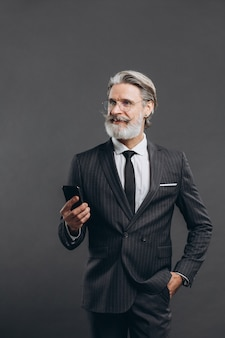 Business and fashionable bearded mature man in a gray suit smiling and talking by phone on the grey wall.