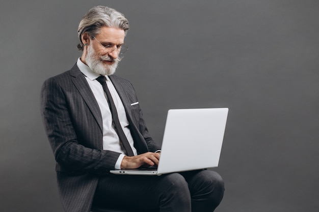 Business and fashionable bearded mature man in a gray suit smiling and using laptop on the grey wall.