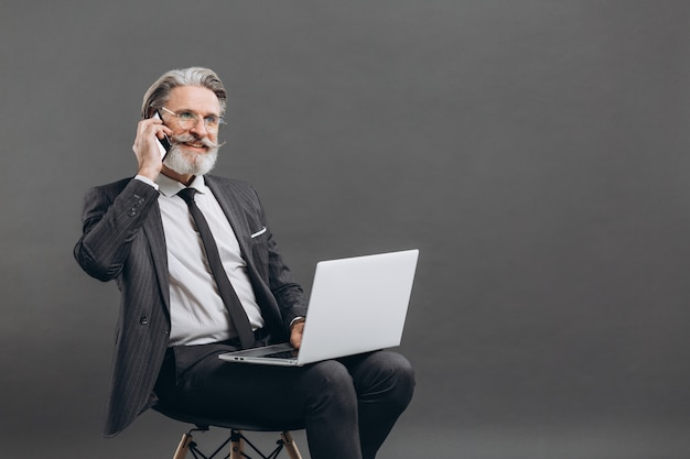 Business and fashionable bearded mature man in a gray suit taking by phone and using laptop on the grey wall.