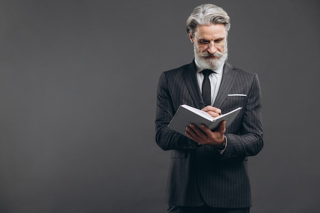 Business and fashionable bearded mature man in a gray suit writing in his notebook copy space on the grey wall.