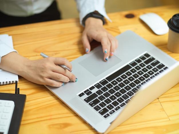 ラップトップ検索情報を使用してビジネスの女性の手がウェブサイトでアイデアを閲覧するクローズアップ