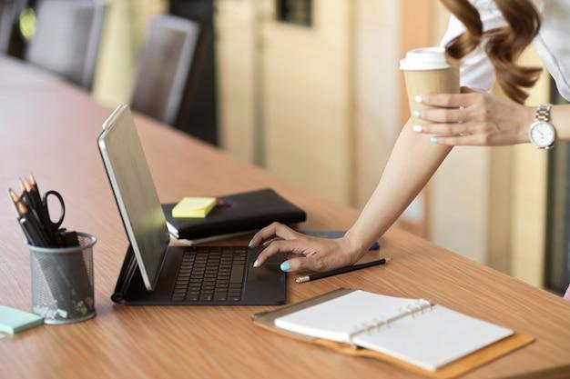 Деловая женщина опирается на офисный стол, набирая на клавиатуре планшета, держа кофе на вынос