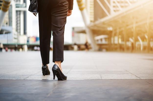街を歩くハイヒールの靴でビジネス女性の脚
