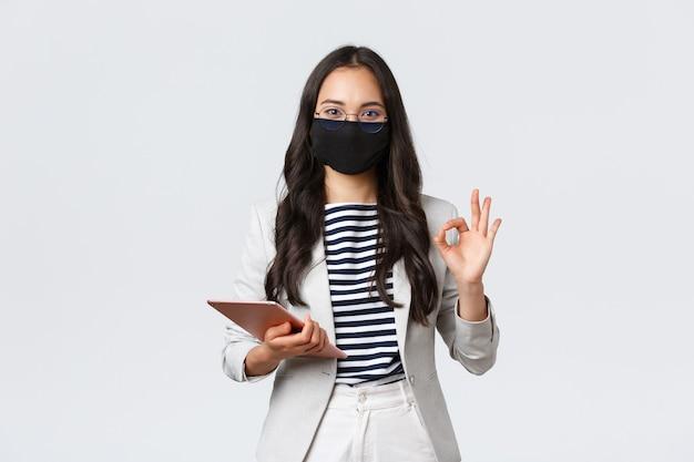 ビジネス、金融、雇用、covid-19ウイルスと社会的距離の概念を防ぎます。デジタルタブレットを持っているアジアの実業家、ウイルスに対する保護マスクを着用し、大丈夫な兆候を示しています