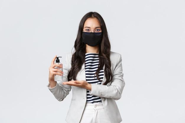ビジネス、金融、雇用、covid-19ウイルスと社会的距離の概念を防ぎます。アジアの女性起業家のフェイスマスクは、人々と一緒に仕事をしているオフィスで手を洗うために手指消毒剤を適用します