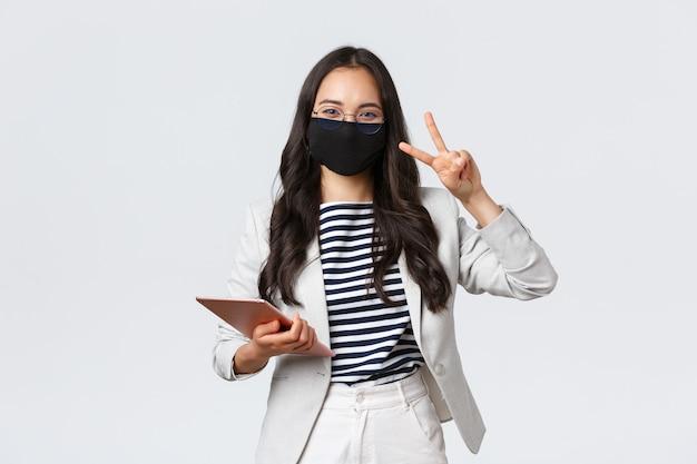 ビジネス、金融、雇用、covid-19ウイルスと社会的距離の概念を防ぎます。陽気な若いアジアのサラリーマン、保護マスクのデジタルタブレットを持つ女性起業家