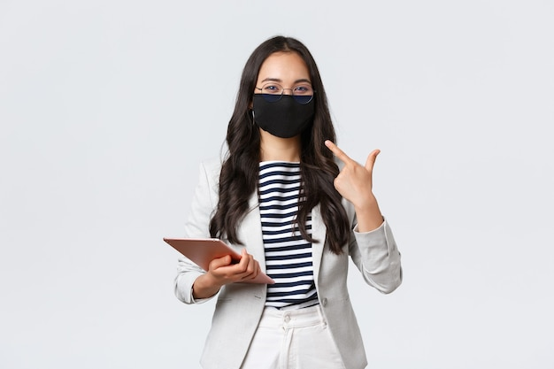 ビジネス、金融、雇用、covid-19ウイルスと社会的距離の概念を防ぎます。顔の保護マスクを指しているデジタルタブレットと笑顔のアジアの実業家