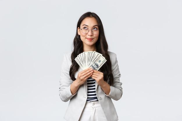 비즈니스, 금융 및 고용, 기업가 및 돈 개념. 꿈꾸는 행복한 여성 사업가는 휴가를 어디로 갈지, 번 돈을 어떻게 투자하고, 현금을 들고, 사려 깊은 곳을 찾는지 생각합니다.