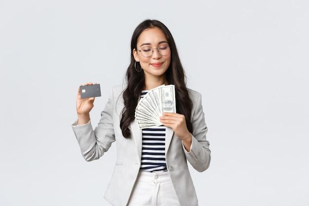 ビジネス、金融、雇用、起業家、お金の概念。成功した満足している実業家は、満足して笑顔で、ドルとクレジットカードを見せて、現金を稼ぎます