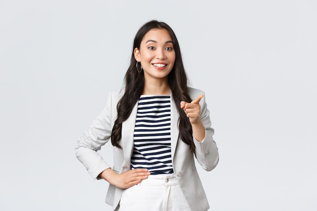 ビジネス、金融、雇用、女性起業家の概念。会議でスピーチをしている成功したアジアの実業家を笑顔で、従業員の素晴らしいアイデアを賞賛し、人差し指は良い点を言います。