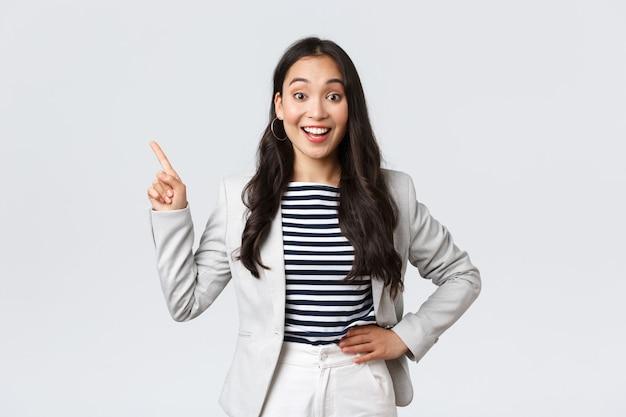 ビジネス、金融、雇用、女性の成功した起業家の概念。広告を表示し、左上隅に指を指している白いスーツで陽気な成功した実業家。