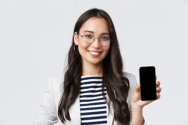 ビジネス、金融、雇用、女性の成功した起業家の概念。スタイリッシュな現代アジアの実業家のクローズアップは、スマートフォンで広告を表示し、モバイルアプリケーションを紹介します