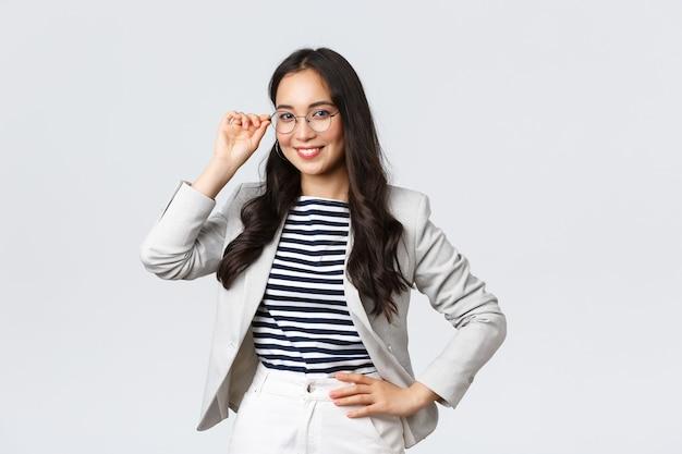 ビジネス、金融、雇用、女性の成功した起業家の概念。眼鏡と白いスーツを着た自信のある実業家は、会議の準備ができて、満足して笑って、決心して立っています