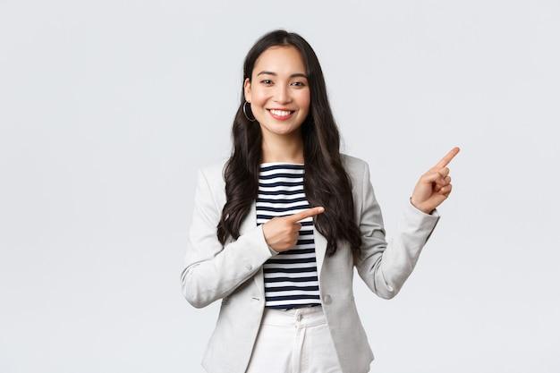 Бизнес, финансы и занятость, концепция успешных женщин-предпринимателей. уверенный профессиональный женский азиатский брокер по недвижимости показывает хорошую сделку, указывая верхний правый угол и улыбается.