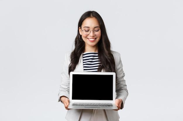 ビジネス、金融、雇用、女性の成功した起業家の概念。プレゼンテーションを示すスーツとメガネの熱狂的な実業家は、ラップトップ画面で彼女のプロジェクトをデモンストレーションします