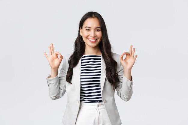 ビジネス、金融、雇用、女性の成功した起業家の概念。親しみやすいプロの笑顔の実業家は、最高の品質またはお得な情報を保証し、大丈夫なジェスチャーを示し、問題はありません。
