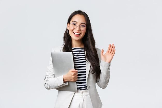 ビジネス、金融、雇用、女性の成功した起業家の概念。新しい同僚に挨拶するフレンドリーな笑顔のオフィスマネージャー。実業家は手を振ってクライアントを歓迎し、ラップトップを保持します