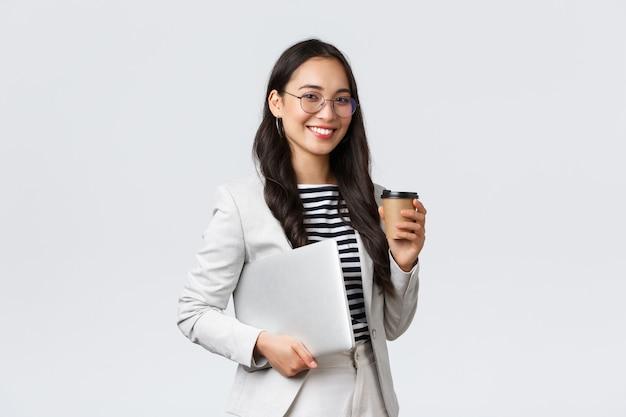 ビジネス、金融、雇用、女性の成功した起業家の概念。次のクライアントに向かう途中で、コーヒーを飲み、ラップトップを運ぶプロの自信を持ってアジアの不動産ブローカー