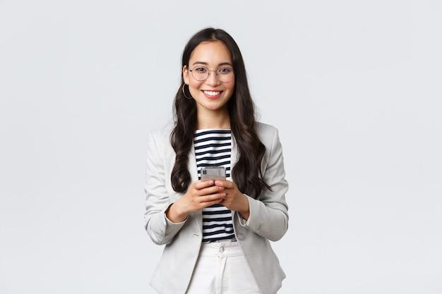 Бизнес, финансы и занятость, концепция успешных женщин-предпринимателей. улыбающаяся приятная азиатская бизнесвумен, брокер по недвижимости в очках, используя мобильный телефон для связи с клиентами