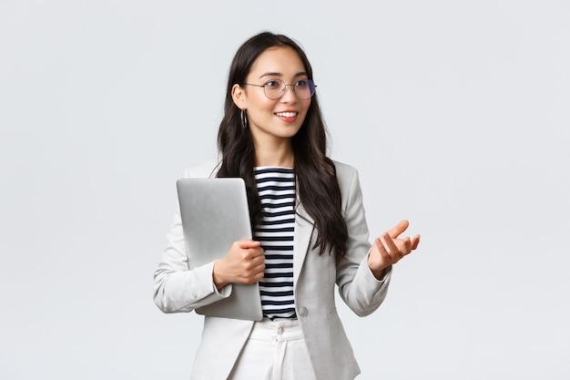 ビジネス、金融、雇用、女性の成功した起業家の概念。笑顔のプロの実業家、クライアントにかなりのことを示す不動産ブローカー、手にラップトップを運ぶ