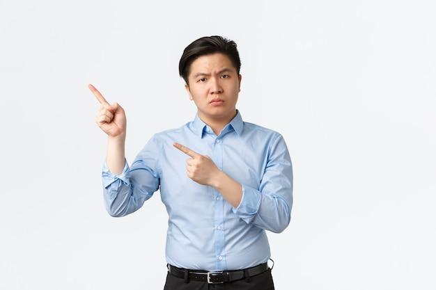 비즈니스, 금융 및 사람 개념입니다. 왼쪽 위 모서리를 가리키는 파란색 셔츠를 입은 실망스러운 인상을 주는 아시아 사업가, 좌절한 직원들, 흰색 배경에 서 있는 불쾌한 서 있는 직원.