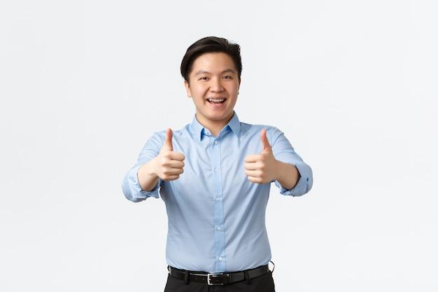 ビジネス、金融、人の概念。熱狂的なハンサムなアジア人男性サラリーマン、歯ブレースを持った従業員、承認で親指を立てる、会社を推薦する、品質を保証する