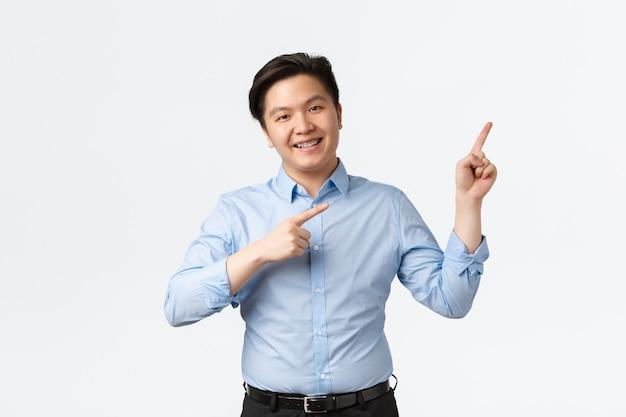 비즈니스, 금융 및 사람 개념입니다. 파란색 셔츠, 치아 교정기, 오른쪽 위 모서리를 가리키는 손가락, 발표, 차트 또는 제품, 흰색 배경을 보여주는 유쾌한 웃는 아시아 세일즈맨.